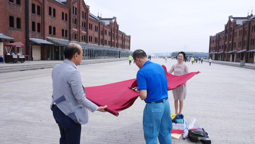 紅のシルクをカットする当社松村社長、礒部、そしてモデルをしてくれた今泉さん。